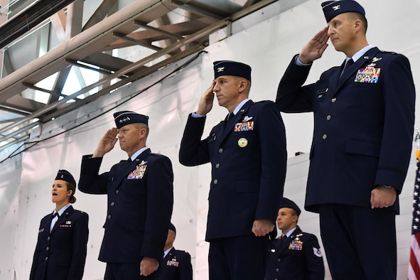 Lt. Gen. Mark Kelly, 12th Air Force commander, Col. Case Cunningham, outgoing 432nd Wing commander and Col. Julian Cheater, incoming 432nd Wing commander, salute during the singing of the national anthem at the 432nd Wing change of command July 6, 2017, at Creech Air Force Base, Nev. During the event, Col. Cheater assumed command from Col. Cunningham in front of a crowd of Airmen, peers and family members. (U.S. Air Force photo/Airman 1st Class James Thompson)