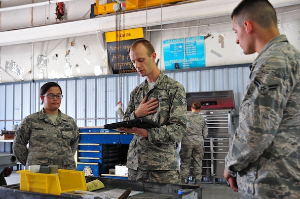 U.S. Air Force Staff Sgt. Joshua Bradley, 20th Equipment Maintenance Squadron (EMS) tactical aircraft maintainer, center, reads a technical order to Senior Airman Keri Brock, left, and Airman 1st Class Ty Lerum, 20th EMS precision guided munitions technicians, at Shaw Air Force Base, S.C., June 27, 2017. The technical order dictates every step the Airmen must take while inspecting munitions. (U.S. Air Force photo by Airman 1st Class Kathryn R.C. Reaves)