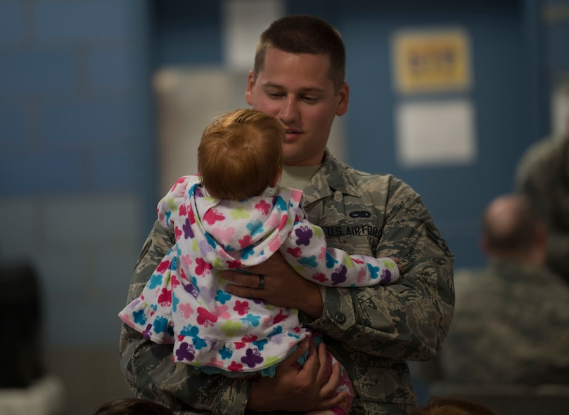 Airman 1st Class Cody Lusk holds Elaina Mullens, the child of Senior Airman Justin Mullins, prior to departing McLaughlin Air National Guard base for a deployment in support of Operation Freedom's Sentinel on June 25, 2017. Lusk and Mullens are aircraft structural maintainers assigned to the 130th Aircraft Maintenance Squadron. (U.S. Air National Guard photo by Tech. Sgt. De-Juan Haley)