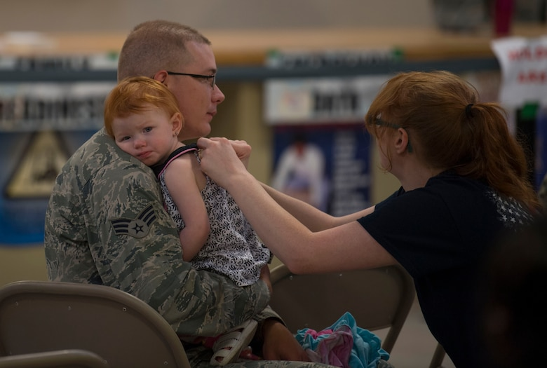 Senior Airman Justin Mullens holds his daughter, Elaina, while his wife looks on, prior to deploying in support of Operation Freedom Sentinel on June 25, 2017 prior to departing McLaughlin Air National Guard base for a deployment in support of Operation Freedom's Sentinel on June 25, 2017. Mullens is an aircraft structural maintainer with the 130th Airlift Wing. (U.S. Air National Guard photo by Tech. Sgt. De-Juan Haley)