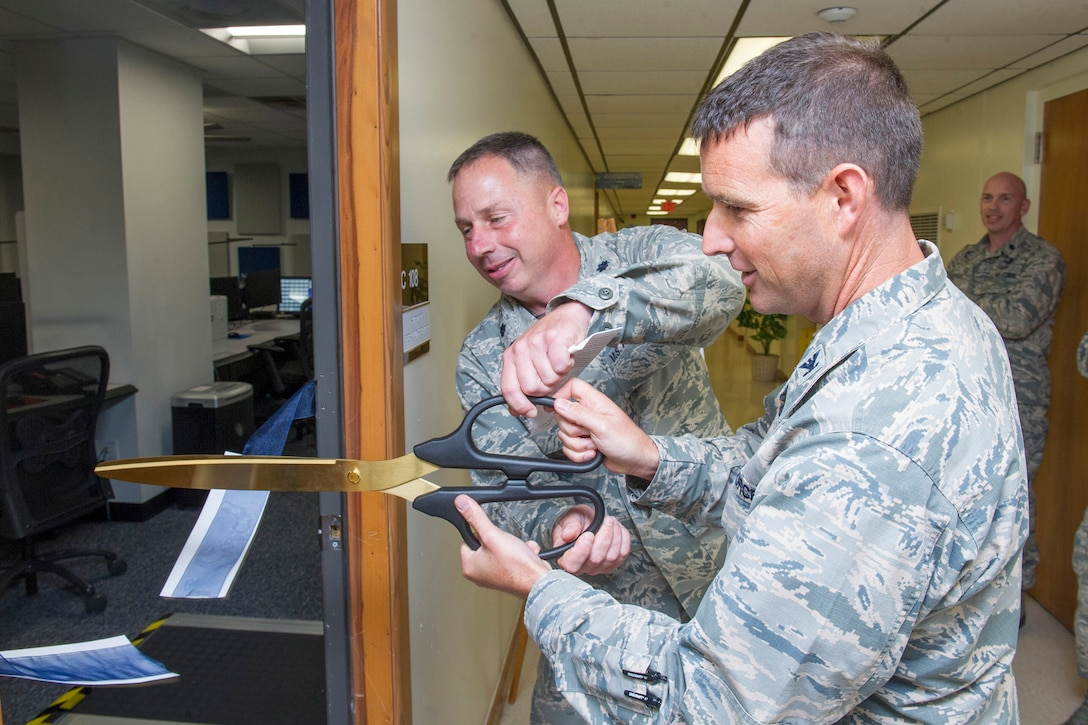 Col. Burton Catledge, 45th Operations Group commander and Lt. Col. Jason Havel, Detachment 3 commander, cut the ribbon to the recently renovated Human Spaceflight Support Operations Center (SOC), to symbolize America's transition from a government operated space program to a blended mission with the addition of commercially-operated crewed spaceflight programs. The $485,000 yearlong project created a state-of-the-art communications hub used for the Department of Defense's human spaceflight support missions from the SOC, which is an extension of the Joint Space Operations Center at Vandenberg AFB, Calif. It hosts a worldwide command and control capability for Department of Defense rescue forces through a combination of radio frequencies, specialized internet applications, texting, satellite and secure and unsecure voice through the SOC's 10 workstations, 20 DOD circuits and 20 NASA specific circuits. (U.S. Air Force photo by Phil Sunkel))
