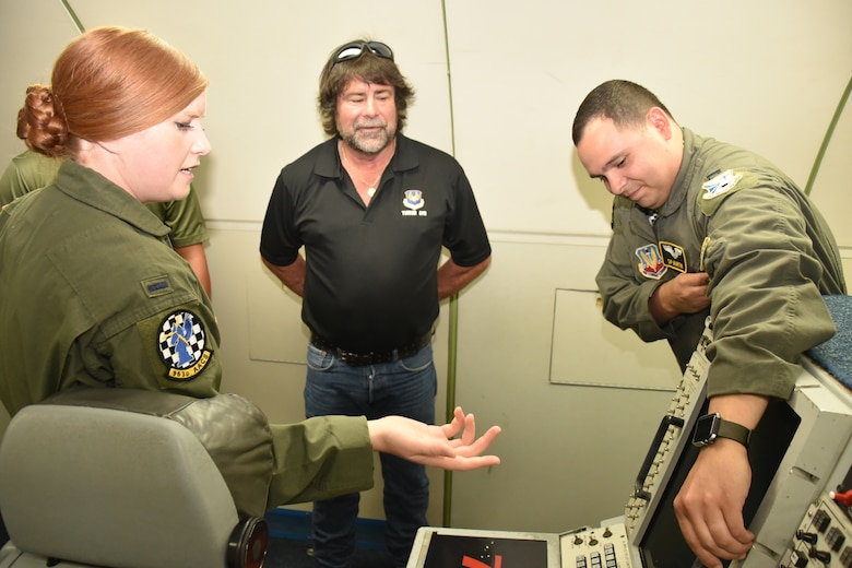 First Lt. Katy Martin, and Capt. Cody Martin, both of the 963rd Airborne Air Control Squadron, describe some of the various equipment on board the E-3 Sentry aircraft to Phil Tinker, grandson of Maj. Gen. Clarence Tinker, whom the base is named after. Tinker also toured the Oklahoma City Air Logistics Complex during his visit June 26-27. (Air Force photo by Ron Mullan)