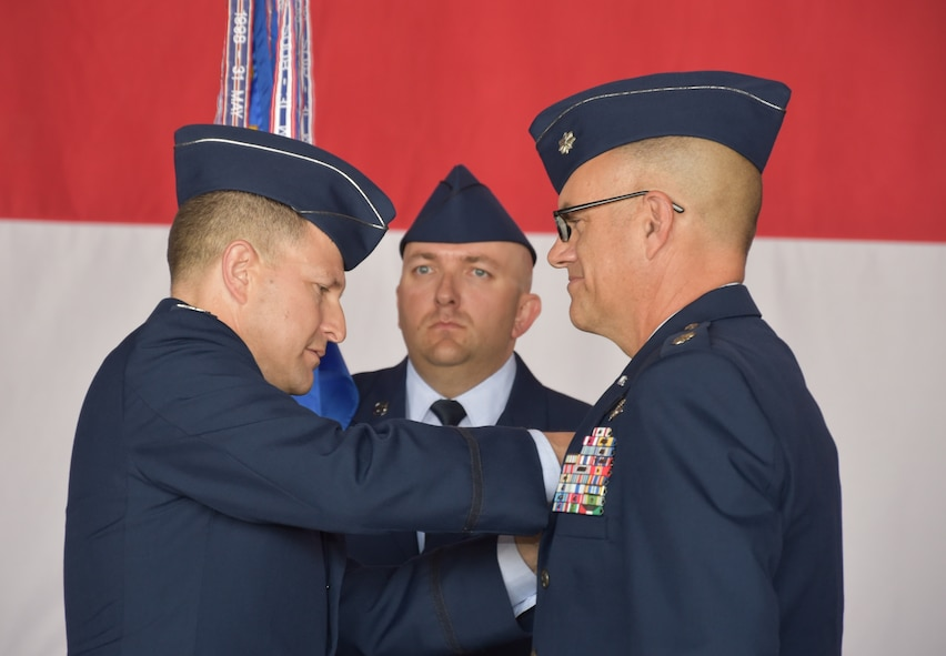 Col. Dominic Setka, 552nd Air Control Group commander, pins the command badge on Lt. Col. Kelly Shelton, 552nd Air Control Networks Squadron commander, during a change of command ceremony June 27. Holding the unit guidon is Master Sgt. Benjamin Jetland, 552nd ACNS first sergeant. (Air Force photo by Ron Mullan)