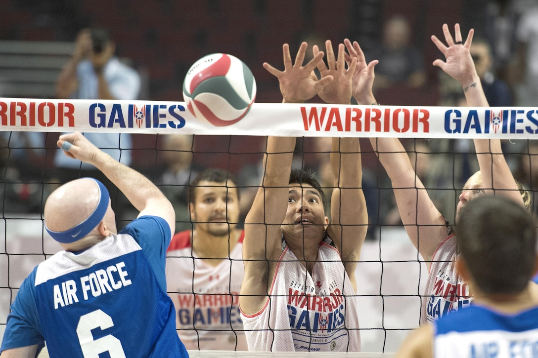 Marine Corps players defend the net in a sitting volleyball game.