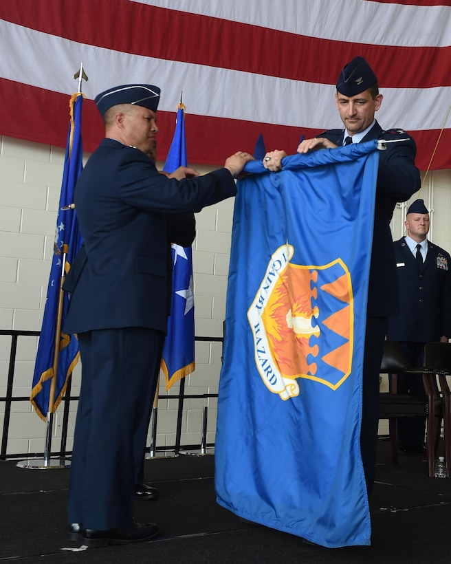 U.S. Air Force Lt. Gen. Giovanni Tuck, 18th Air Force Commander, and Col. Stephen Hodge, 317th Airlift Group commander, furl the 317th AG unit flag at Dyess Air Force Base, Texas July 6, 2017. The 317th Airlift Group was deactivated and subsequently activated as the 317th Airlift Wing. (U.S. Air Force photo by Senior Airman Alexander Guerrero)