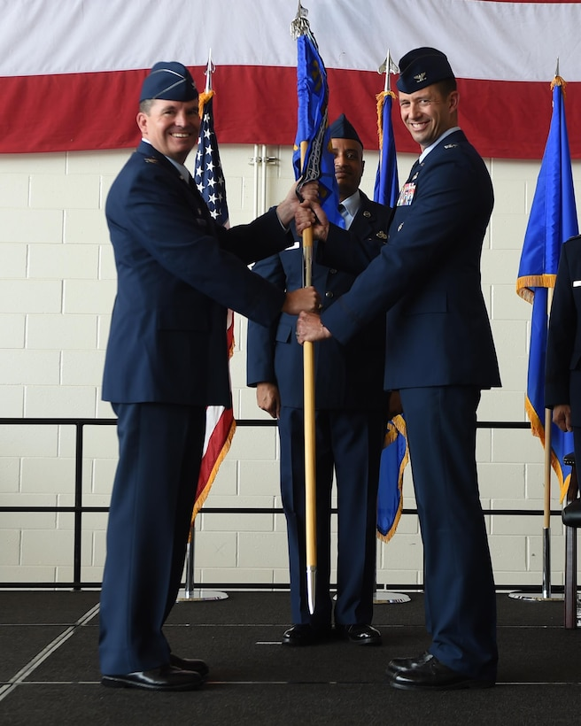 U.S. Air Force Col. David Owens, 317th Airlift Wing commander, hands a guidon to Col. William Maxwell, 317th Maintenance Group commander, at Dyess Air Force Base, Texas, July 6, 2017. The 317th MXG was activated to help support and maintain the C-130J Super Hercules' of the 317th AW and their tactical airlift mission at Dyess. (U.S. Air Force photo by Senior Airman Alexander Guerrero)