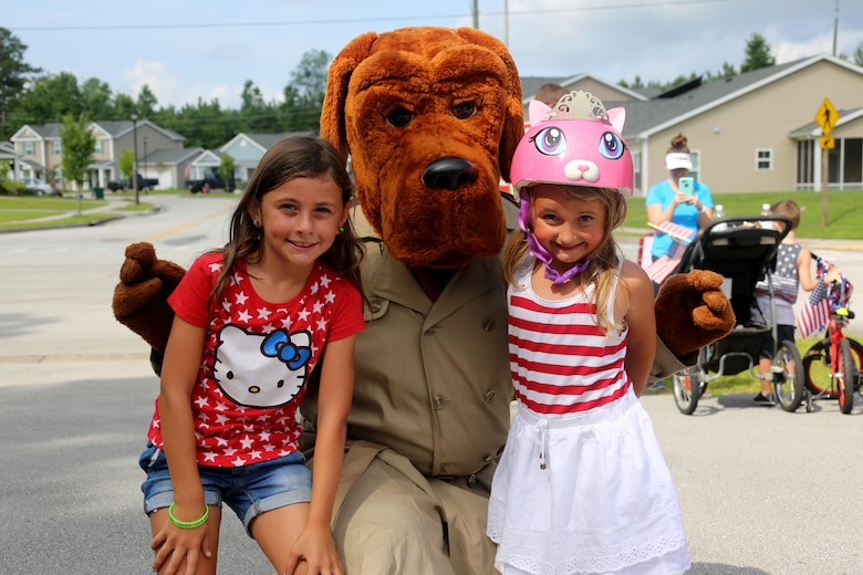 Ashlyn, 8, left, and Adelyn, 5, pose with McGruff the Crime Dog during the first Independence Day Youth Parade at Marine Corps Air Station Cherry Point, N.C., July 4, 2017. Nearly 100 members of the Cherry Point community joined in on the red, white and blue parade. The mile-long bike parade was organized by housing resident Caitlin Chemelewski as a patriotic and fun event for the kids, and to bring the MCAS Cherry Point community together on Independence Day. (U.S. Marine Corps photo by Cpl. Jason Jimenez/ Released)