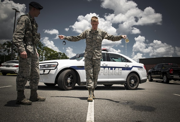 Airman 1st Class Erick Requadt, 23d Wing photojournalist, simulates a field sobriety test, July 7, 2017, at Moody Air Force Base, Ga. When an Airman receives a driving under the influence charge, they are eligible to receive both a civilian conviction if caught off base, as well as a punishment given at their commander's discretion. The final sentence could cost thousands of dollars in fines, suspension of their license, negative paperwork, administrative demotion, and possible loss of career or reclassification. (U.S. Air Force photo illustration by Airman 1st Class Lauren M. Sprunk)