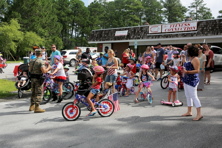 Families ready themselves to start a bike parade during the first Independence Day Youth Parade at Marine Corps Air Station Cherry Point, N.C., July 4, 2017. The MCAS Cherry Point Provost Marshal's Office ensured the Independence Day fun was enjoyed safely with their vehicles leading participants through the mile-long route.  Cherry Point's very own McGruff the Crime Dog and Sparky the Fire Dog interacted with children. Nearly 100 members of the Cherry Point community participated in the red, white and blue parade. (U.S. Marine Corps photo by Cpl. Jason Jimenez/ Released)