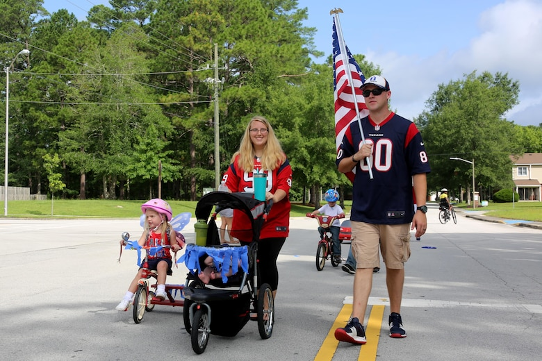 Community members parade through their neighborhood during the first Independence Day Youth Parade at Marine Corps Air Station Cherry Point, N.C., July 4, 2017. Escorted by Cherry Point police, the event catered to younger family members, but encouraged the larger community to come together. Nearly 100 Cherry Point community residents gathered for the festivities. (U.S. Marine Corps photo by Cpl. Jason Jimenez/ Released)