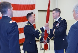 Brig. Gen. Mark Toy, commander of the Great Lakes and Ohio River Division, passes the Nashville District colors to Lt. Col. Cullen A. Jones, incoming commander, during a ceremony July 7, 2017 at the Tennessee National Guard Armory. He becomes the 65th commander in the district's 127 year history. Looking on is Nashville District Deputy District Engineer for Program Management Patty Coffey (far left), and outgoing commander, Lt. Col. Stephen F. Murphy (Center).