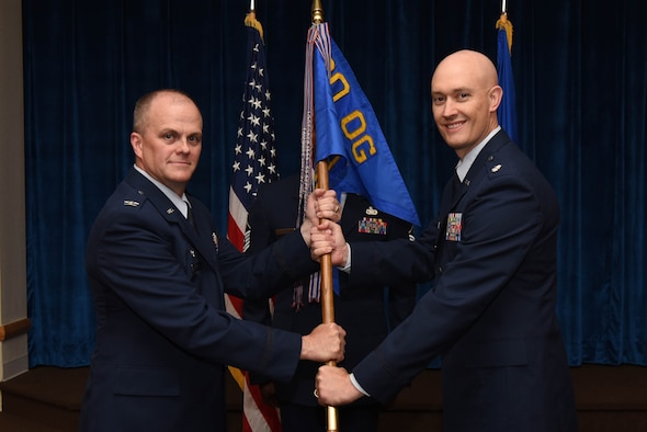 Col. Todd Sauls, 90th Operations Group commander, passes the guidon to Lt. Col. Christopher Maroney, 90th Operations Support Squadron commander, during the 90th OSS change of command ceremony at F.E. Warren Air Force Base, Wyo., July 7, 2017. The ceremony signified the transition of command from Lt. Col. John Hundley. (U.S. Air Force photo by Airman 1st Class Breanna Carter)