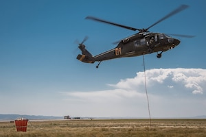 A Wyoming Army National Guard UH-60 Black Hawk helicopter takes off from Laramie Regional Airport July 6, 2017, to assist in fighting the Keystone Fire. Visible at left is the helicopter's water bucket.