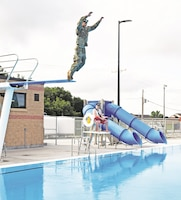 Fort Riley Garrison Command Sgt. Maj. James Collins jumps from the high diving board into the pool during the grand opening of the Custer Hill Aquatic Park June 30. Following the opening, the park was free for the day with the Splish Splash Beach Bash party featuring music, food and more as Directorate of Family and Morale, Welfare and Recreation and USO Fort Riley partnered to make it possible.