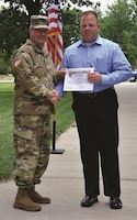Tom Pendleton, chief of plans, Directorate of Plans, Training, Mobilization and Security, accepts Chris Hallenbeck's certificate of appreciation from Col. John D. Lawrence, Fort Riley garrison commander, after Hallenbeck was announced as the Employee of the Month for May during a ceremony June 30 at Ware Parade Field.