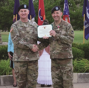 Lt. Col. Brian D. Beiner, right, outgoing commander of the Army Field Support Battalion-Riley, is presented the Meritorious Service Medal by Col. Eric P. Shirley, commander of the 407th Army Field Support Brigade, during a ceremony June 30.