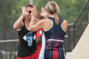 Marine Corps veteran Sarah Rudder, left, high fives Royal Air Force veteran Flight Lieutenant Jannine Church during practice for track competition during the 2017 Department of Defense (DoD) Warrior Games in Chicago, Ill., June 30, 2017. Rudder was helping Church with her race starts. The DoD Warrior Games are an annual event allowing wounded, ill and injured service members and veterans to compete in Paralympic-style sports including archery, cycling, field, shooting, sitting volleyball, swimming, track and wheelchair basketball.    (DoD photo by Roger L. Wollenberg)