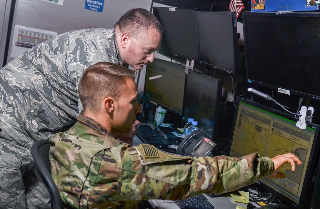 Staff Sgt. Michael Clevenger, a weather forecaster with the 609th Air Operations Center, and Maj. Ryan Willis, cell chief of the 609th AOC weather specialty team (WST), discuss weather patterns over Southwest Asia, June 7, 2017, in the Combined Air Operations Center at Al Udeid Air Base, Qatar. The WST provides daily and up-to-the-minute weather updates to a diverse multinational Coalition team that plans, coordinates, and develops air operations supporting Operation Inherent Resolve and other military operations in the region. (U.S. Air Force photo by Staff Sgt. Alexander W. Riedel)