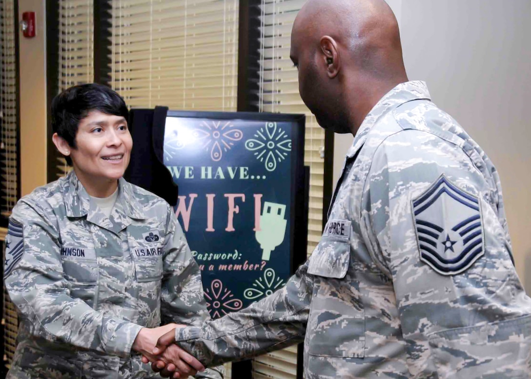 Chief Master Sgt. Imelda B. Johnson, 94th Airlift Wing command chief master sergeant, greets an Airman at the dining facility here, May 6, 2017. Chief Johnson is the newest command chief assigned to the 94th AW. (U.S. Air Force photo by Airman 1st Class Justin Clayvon)