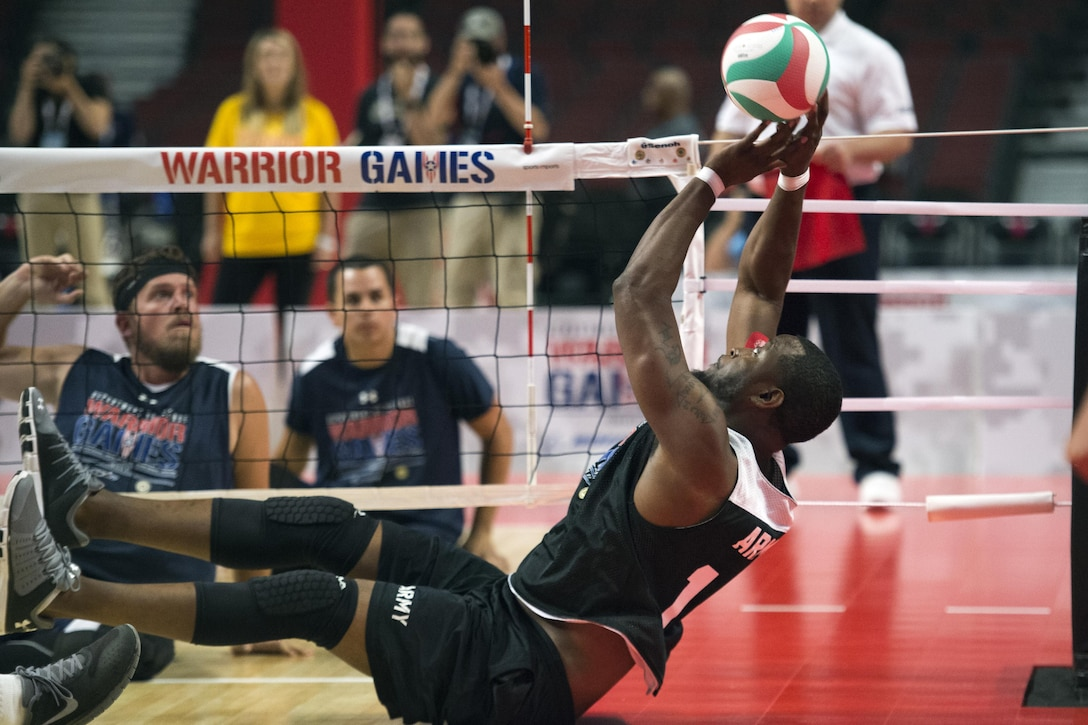 An army veteran reaches for a volleyball seated on the floor.