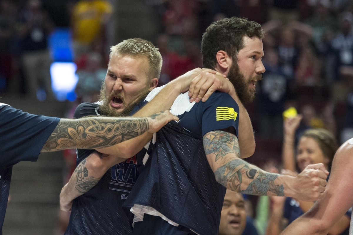 Two Navy veterans celebrate winning gold in sitting volleyball.
