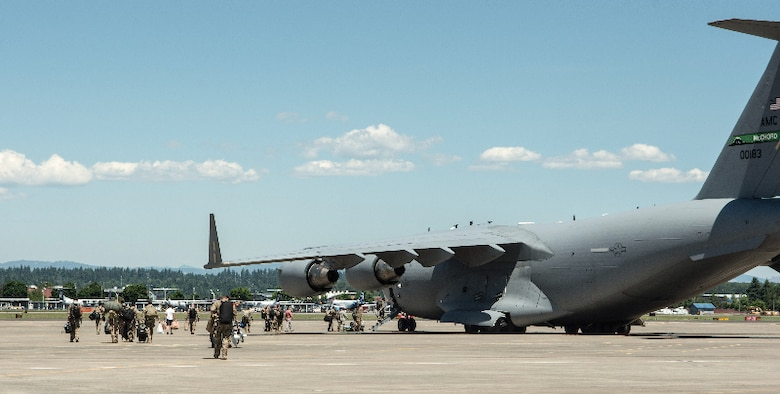 Members of the 304th Rescue Squadron walk to a C-17 in preparation for the unit's largest deployment in its 60-year history, May 27, 2017, Portland, Oregon. (U.S. Air Force photo by Staff Sgt. Schaeffer Bonner)