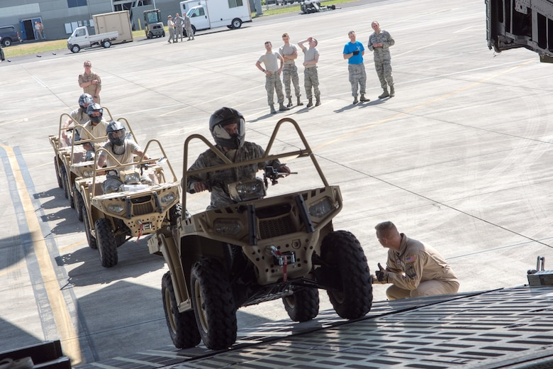 Members of the 304th Rescue Squadron drive all-terrain vehicles onto a C-5 Galaxy in preparation for the unit's largest deployment in its 60-year history, May 27, 2017, Portland, Oregon. (U.S. Air Force photo by Staff Sgt. Schaeffer Bonner)