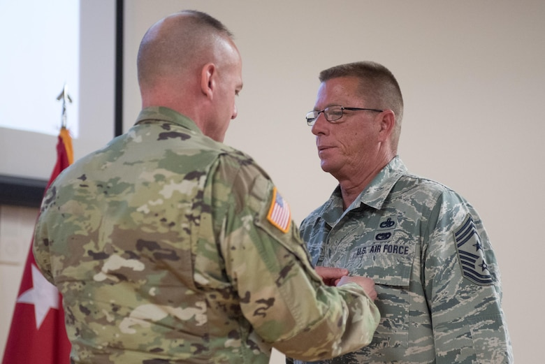 Army Maj. Gen. Stephen Hogan (left), the adjutant general for Kentucky, pins the Legion of Merit onto Chief Master Sgt. Jeffrey Moore (right), the outgoing state command chief master sergeant, during Moore's retirement ceremony at the Kentucky Air National Guard base in Louisville, Ky., on May 20, 2017. Moore is retiring after 35 years of service to the Kentucky Air National Guard and United States Air Force. (U.S. Air National Guard photo by Staff Sgt. Joshua Horton)