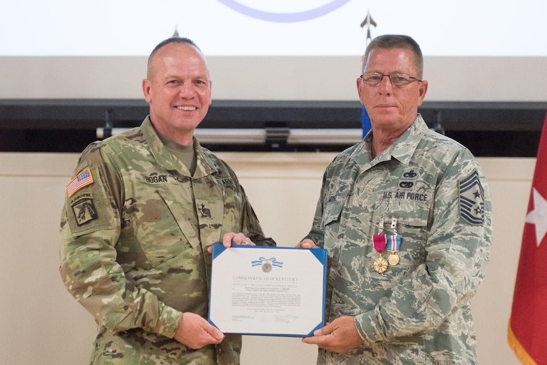 Chief Master Sgt. Jeffrey Moore (right), the outgoing state command chief master sergeant, receives the Distinguished Service Medal from Army Maj. Gen. Stephen Hogan (left), the adjutant general for Kentucky, during Moore's retirement ceremony at the Kentucky Air National Guard base in Louisville, Ky., on May 20, 2017. Moore is retiring after 35 of service to the Kentucky Air National Guard and United States Air Force. (U.S.  Air National Guard photo by Staff Sgt. Joshua Horton)