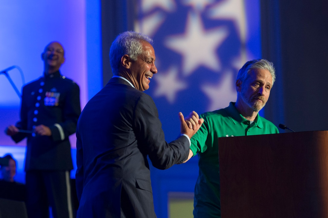 Rahm Emanuel and Jon Stewart shake hands on stage.