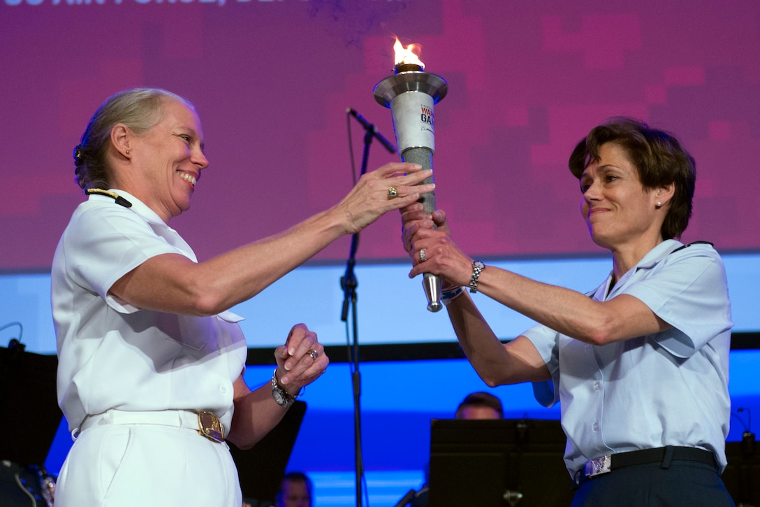 Military leaders exchange the Warrior Games torch during closing ceremonies.