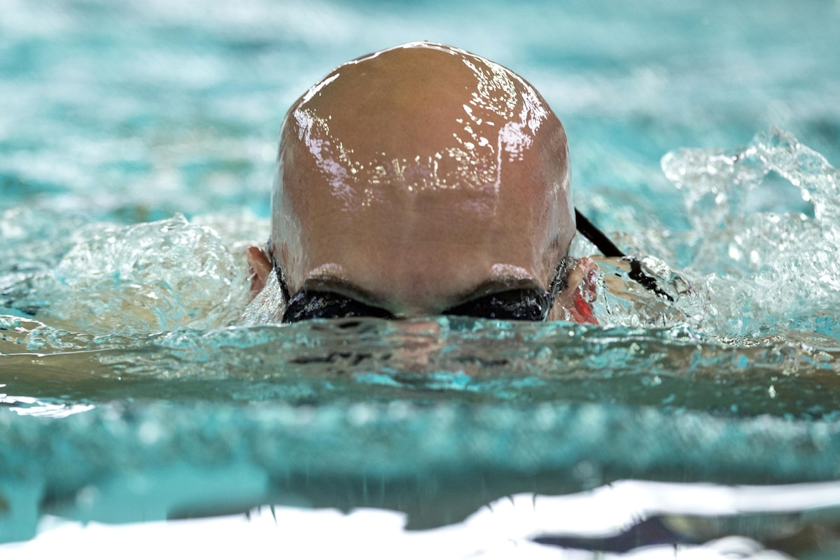 A sailor with half his bald head submerged swims the breaststroke.