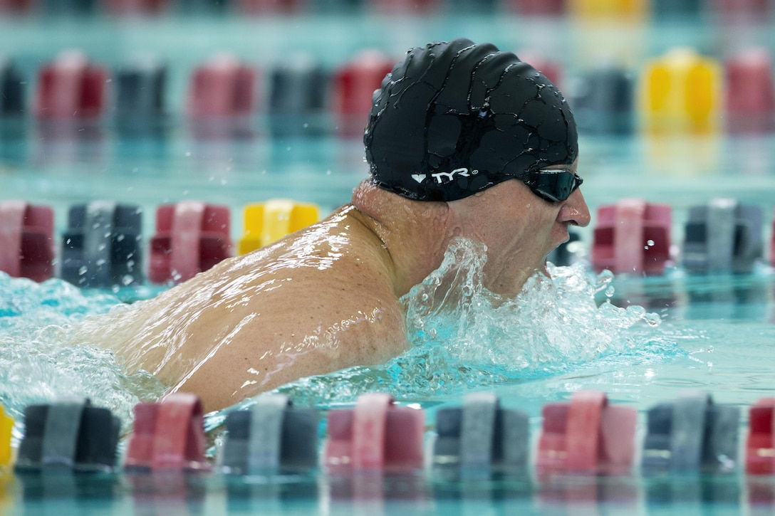 A swimmer breaks the surface during a breaststroke race.