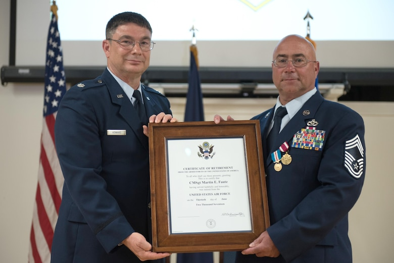 Chief Master Sgt. Martin E. Fautz (right), outgoing chief enlisted manager for the 123rd Civil Engineer Squadron, is presented with his certificate of retirement by retired Lt. Col. Phillip Howard, former commander of the squadron, during Fautz's retirement ceremony at the Kentucky Air National Guard base in Louisville, Ky., on June 10, 2017. Fautz is retiring after more than 30 years of service to the Kentucky Air National Guard. (U.S. Air National Guard photo by Staff Sgt. Joshua Horton)