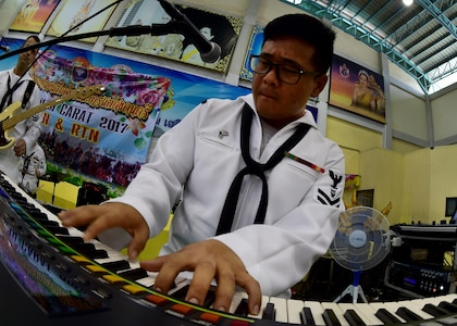 170602-N-QV906-069 PATTAYA, Thailand (June 2, 2017) Navy Musician 2nd Class Daniel Park, of the U.S. 7th Fleet Band, Orient Express, jams out during a performance at Pattaya City No. 8 School as part of Cooperation Afloat Readiness and Training Thailand 2017 in Pattaya, Thailand, June 2. Cooperation Afloat Readiness and Training (CARAT) is a series of PACOM sponsored, U.S. Pacific Fleet led bilateral exercises held annually in South and Southeast Asia to strengthen relationships and enhance force readiness. CARAT exercise events cover a broad range of naval skill areas and disciplines including surface, undersea, air and amphibious warfare; maritime security operations; riverine, jungle and explosive ordnance disposal operations; combat construction; diving and salvage; search and rescue; maritime patrol and reconnaissance aviation; maritime domain awareness; military law, public affairs and military medicine; and humanitarian assistance, disaster response. (U.S. Navy photo by Mass Communication Specialist 1st Class Micah Blechner/RELEASED)