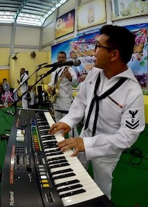170602-N-QV906-132 PATTAYA, Thailand (June 2, 2017) Navy Musician 2nd Class Daniel Park, of the U.S. 7th Fleet Band, Orient Express, jams out during a performance at Pattaya City No. 8 School as part of Cooperation Afloat Readiness and Training Thailand 2017 in Pattaya, Thailand, June 2. Cooperation Afloat Readiness and Training (CARAT) is a series of PACOM sponsored, U.S. Pacific Fleet led bilateral exercises held annually in South and Southeast Asia to strengthen relationships and enhance force readiness. CARAT exercise events cover a broad range of naval skill areas and disciplines including surface, undersea, air and amphibious warfare; maritime security operations; riverine, jungle and explosive ordnance disposal operations; combat construction; diving and salvage; search and rescue; maritime patrol and reconnaissance aviation; maritime domain awareness; military law, public affairs and military medicine; and humanitarian assistance, disaster response. (U.S. Navy photo by Mass Communication Specialist 1st Class Micah Blechner/RELEASED)