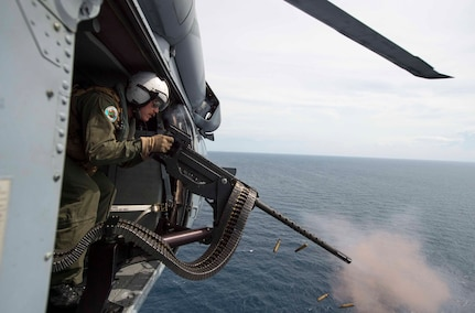 """170603-N-PD309-1067 GULF OF THAILAND (June 3, 2017) Naval Aircrewman (Helicopter) 2nd Class Nicholas Lovelace, assigned to the """"Wildcards"""" of Helicopter Sea Combat Squadron 23 aboard littoral combat ship USS Coronado (LCS 4), shoots a target with a .50 caliber machine gun as part of a gunnery exercise with the Royal Thai Navy during Cooperation Afloat Readiness and Training (CARAT) Thailand. CARAT is a series of Pacific Command-sponsored, U.S Pacific Fleet-led bilateral exercises held annually in South and Southeast Asia to strengthen relationships and enhance force readiness. CARAT exercise events cover a broad range of naval skill areas and disciplines including surface, undersea, air, and amphibious warfare; maritime security operations; riverine, jungle, and explosive ordnance disposal operations; combat construction; diving and salvage; search and rescue; maritime patrol and reconnaissance aviation; maritime domain awareness; military law, public affairs and military medicine; and humanitarian assistance and disaster response. (U.S. Navy photo by Mass Communication Specialist 3rd Class Deven Leigh Ellis/Released)"""