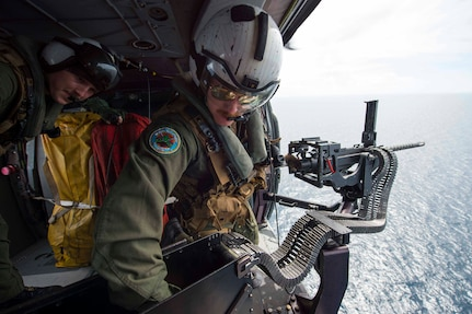 """170603-N-PD309-1142 GULF OF THAILAND, Thailand (June 3, 2017) Naval Aircrewman (Helicopter) 2nd Class Nicholas Lovelace, right, assigned to the """"Wildcards"""" of Helicopter Sea Combat Squadron 23 aboard littoral combat ship USS Coronado (LCS 4), loads rounds into a .50 caliber machine gun during a gunnery exercise with the Royal Thai Navy in support of Cooperation Afloat Readiness and Training (CARAT) Thailand. CARAT is a series of Pacific Command-sponsored, U.S Pacific Fleet-led bilateral exercises held annually in South and Southeast Asia to strengthen relationships and enhance force readiness. CARAT exercise events cover a broad range of naval skill areas and disciplines including surface, undersea, air, and amphibious warfare; maritime security operations; riverine, jungle, and explosive ordnance disposal operations; combat construction; diving and salvage; search and rescue; maritime patrol and reconnaissance aviation; maritime domain awareness; military law, public affairs and military medicine; and humanitarian assistance and disaster response. (U.S. Navy photo by Mass Communication Specialist 3rd Class Deven Leigh Ellis/Released)"""