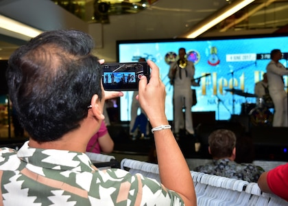 170604-N-QV906-080 PATTAYA, Thailand (June 4, 2017) A member of the crowd records the U.S. 7th Fleet Band, Orient Express, jam out during a performance at Golden Plaza Mall in Pattaya, Thailand, while participating in Cooperation Afloat Readiness and Training Thailand 2017 June 3.  Cooperation Afloat Readiness and Training (CARAT) is a series of PACOM sponsored, U.S. Pacific Fleet led bilateral exercises held annually in South and Southeast Asia to strengthen relationships and enhance force readiness. CARAT exercise events cover a broad range of naval skill areas and disciplines including surface, undersea, air and amphibious warfare; maritime security operations; riverine, jungle and explosive ordnance disposal operations; combat construction; diving and salvage; search and rescue; maritime patrol and reconnaissance aviation; maritime domain awareness; military law, public affairs and military medicine; and humanitarian assistance, disaster response. (U.S. Navy photo by Mass Communication Specialist 1st Class Micah Blechner/RELEASED)