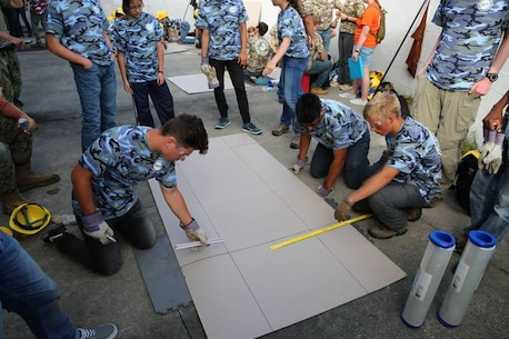 From June 17 to June 21, 2017 high school students from the Society of American Military Engineers (SAME) spent a week at Courthouse Bay, Camp Lejeune, N.C. participating in various engineer themed activities. Here a group of students are measuring and scoring cardboard in order to assist in shaping their cardboard amphibious vehicles.  Once the amphibious vehicles are complete they will be tested in a shallow inlet.