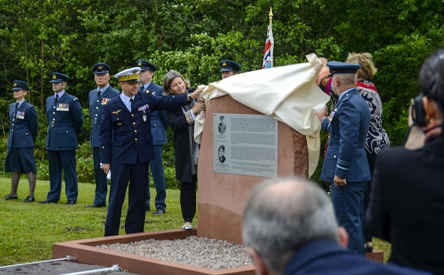 "Members of the French and Royal Air Forces assist family members of Squadron Leader Roger Bushell, Royal Air Force, and Sous-Lieutenant Bernard Scheidhauer, Free French Air Force, unveil the memorial dedicated to the two men outside the West Gate of Ramstein Air Base, Germany, July 1, 2017. The two airmen were the masterminds behind the ""Great Escape"" that took place March 24, 1944. During the Escape, 76 Allied airmen escaped from the prisoner of war camp Stalag Luft III at Żagań, Poland. Although, they only made it as far as Saarbrücken, Germany, they were arrested on March 26, and interrogated. On March 29, under the pretext of being returned to their prison camp, Bushell and Scheidhauer were driven to a bridge near Ramstein and killed. Throughout the following days, 48 of their fellow escapees were executed. The commemorative stone was made possible through the support and efforts of the German, U.S., British, and French communities. (U.S. Air Force photo by Staff Sgt. Timothy Moore)"