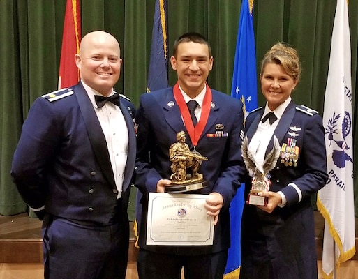 Senior Airman Jonathan Francis, 433rd Operations Support Squadron intelligence flight, Maj. Wesley Lowery, 433rd OSS chief, and Lt. Col. Kari Hill, 433rd OSS commander, display Francis' Airman Leadership School awards July 5,2017 at Joint Base San Antonio-Lackland, Texas. Francis  was awarded the Distinguished Graduate and the Commandant's Award. (Courtesy photo by Ester Francis)