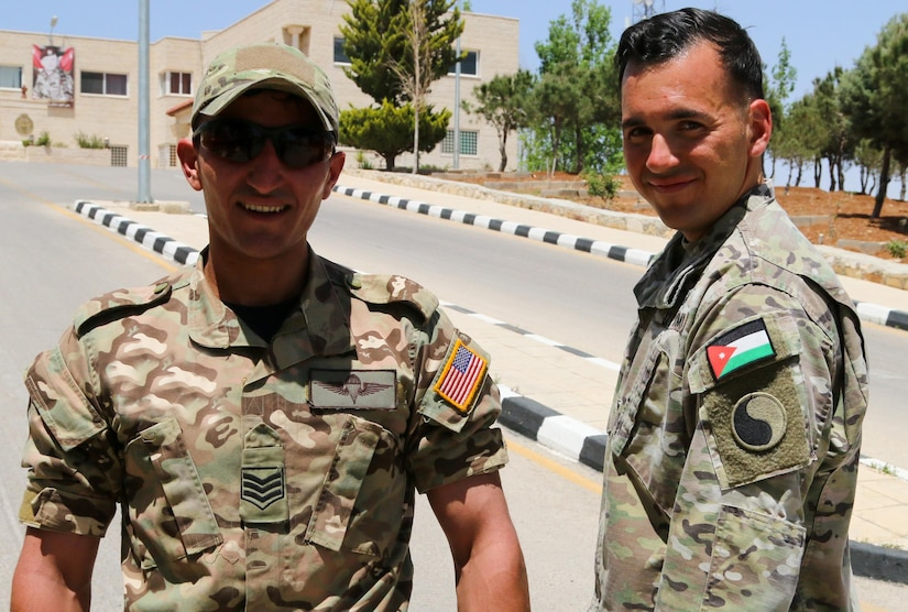 Sgt. 1st Class Donald Spring, a Virginia National Guard Soldier assigned to the 29th Infantry Division, and a staff sergeant from the Jordan Armed Forces-Arab Army (JAF) Special Operations Command pose after exchanging their countries' flags following the Jordanian-American Military Fitness Challenge May 10, 2017, near Amman, Jordan. The challenge consisted of air-squats, sit-ups, push-ups, and burpees. The event, which was recorded for broadcast on social media, highlighted the physical fitness of both JAF and U.S. Soldiers and challenged the Jordanian public to beat the Soldiers' time. (U.S. Army photo by Sgt. 1st Class Kenneth Upsall)