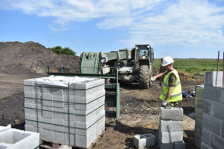 A Soldier of the 225th Field Engineers, U.K. Royal Monmouthshire Royal Engineers (Militia), ground guides Staff Sgt. Benjamin Sykora of the 926th Engineer Brigade, United States Army Reservse, as he moves construction materials. The concrete blocks are for a Light Demolition Range. The construction project is a part of Operation Resolute Castle 2017 at the Joint National Training Center, Cincu, Romania. Resolute Castle is an exercise strengthening the NATO alliance and enhancing its capacity for joint training and response to threats within the region.
