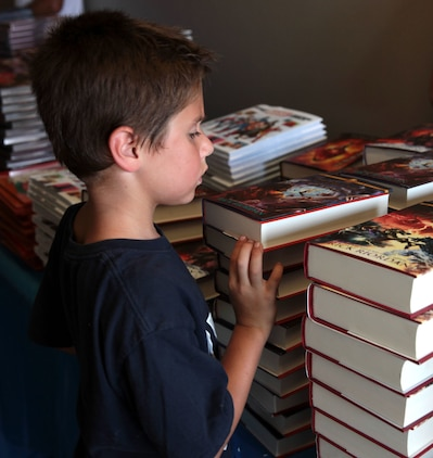 A young child looks over donated books to decide which to keep during Books on Bases, Camp Pendleton, Calif., July 8th, 2017. Books on Bases brings books to military children and is a part of Blue Star Families' and The Walt Disney Company's  ongoing effort to to support military families across the nation. (U.S. Marine Corps Photo by LCpl. Dylan Chagnon)