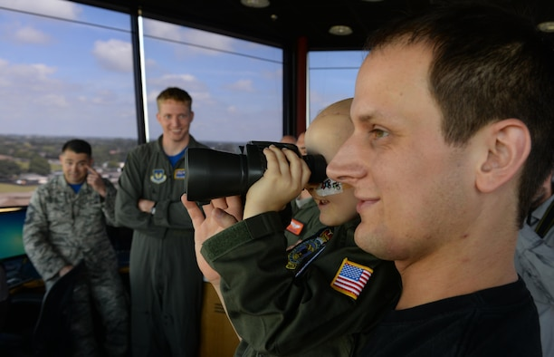 Martin Davidson, holds his son, Jay, while he looks through binoculars in the air traffic control tower during a Pilot for a Day visit July 7, 2017, on RAF Mildenhall, England. Jay was diagnosed with high-risk medulloblastoma in January 2017 and was offered the opportunity to visit the base to view aircraft and meet aircrew. (U.S. Air Force photo by Staff Sgt. Micaiah Anthony)