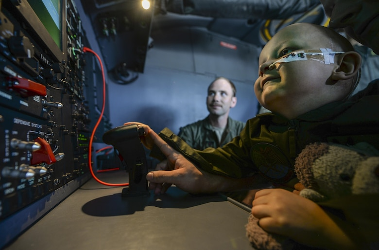 Jay Davidson moves an electro-optical infrared camera on an MC-130J Commando II with the help of his father, Martin, during a Pilot for a Day visit July 7, 2017, at RAF Mildenhall, England. Jay was diagnosed with high-risk medulloblastoma in January 2017. After seven months of chemotherapy, Jay's doctors told him the brain tumors have gone into remission. (U.S. Air Force photo by Staff Sgt. Micaiah Anthony)