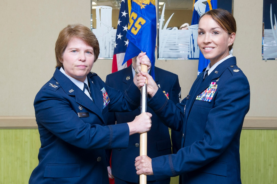 Col. Julie Stola, 45th Space Wing Medical Group commander, presents Lt. Col. Tara Lovell, 45th Medical Support Squadron commander, with the 45th MDSS guidon during a change of command ceremony July 10, 2017, at Patrick Air Force Base, Fla. Changes of command are a military tradition representing the transfer of responsibilities from the presiding officials to the upcoming official. (U.S. Air Force photo/Phil Sunkel)
