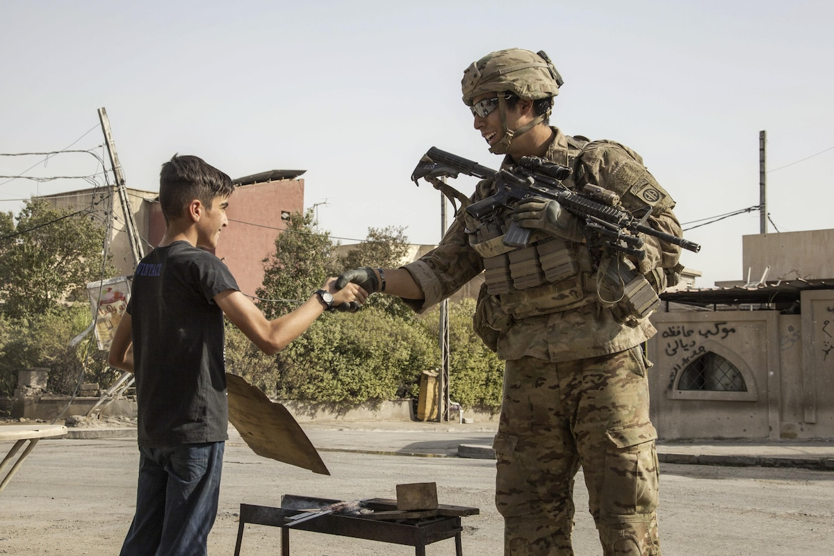 A U.S. soldier shakes hands with a boy in Iraq