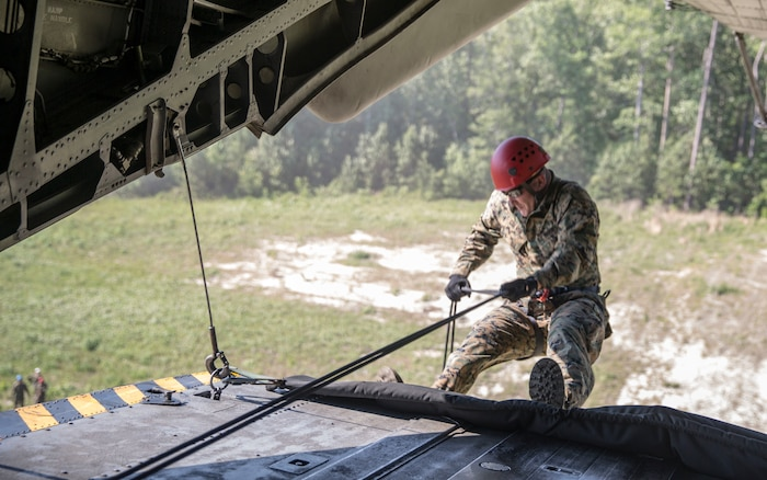 Staff Sgt. Jerry Colvin rappels out of a CH-53 Super Stallion during a ceremony at Stone Bay, a Camp Lejeune satellite training area, N.C., May 17, 2017.  The ceremony marks the reopening of Landing Zone Vulture, which closed Sept. 2, 2015 after a CH-53 crashed resulting in the death of one Marine.  The instructors took the opportunity to memorialize their fallen Marine, Staff Sgt. Jonathan Lewis, through the sustainment rappel. Colvin is with EOTG, II Marine Expeditionary Force Headquarters Group.